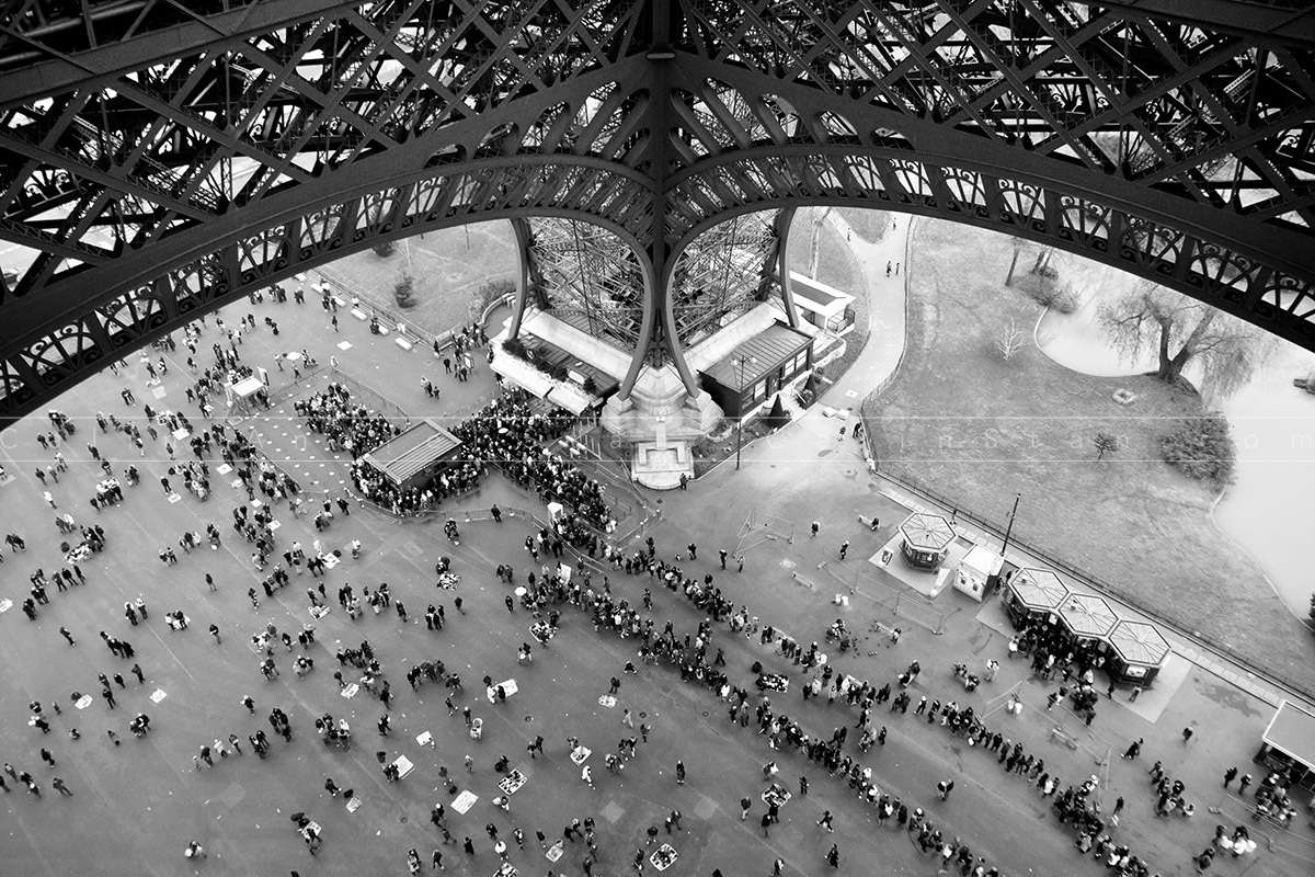 People standing in line under the Eiffel Tower in Paris