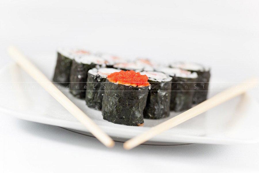 Sushi menu and chopsticks on plate, white background