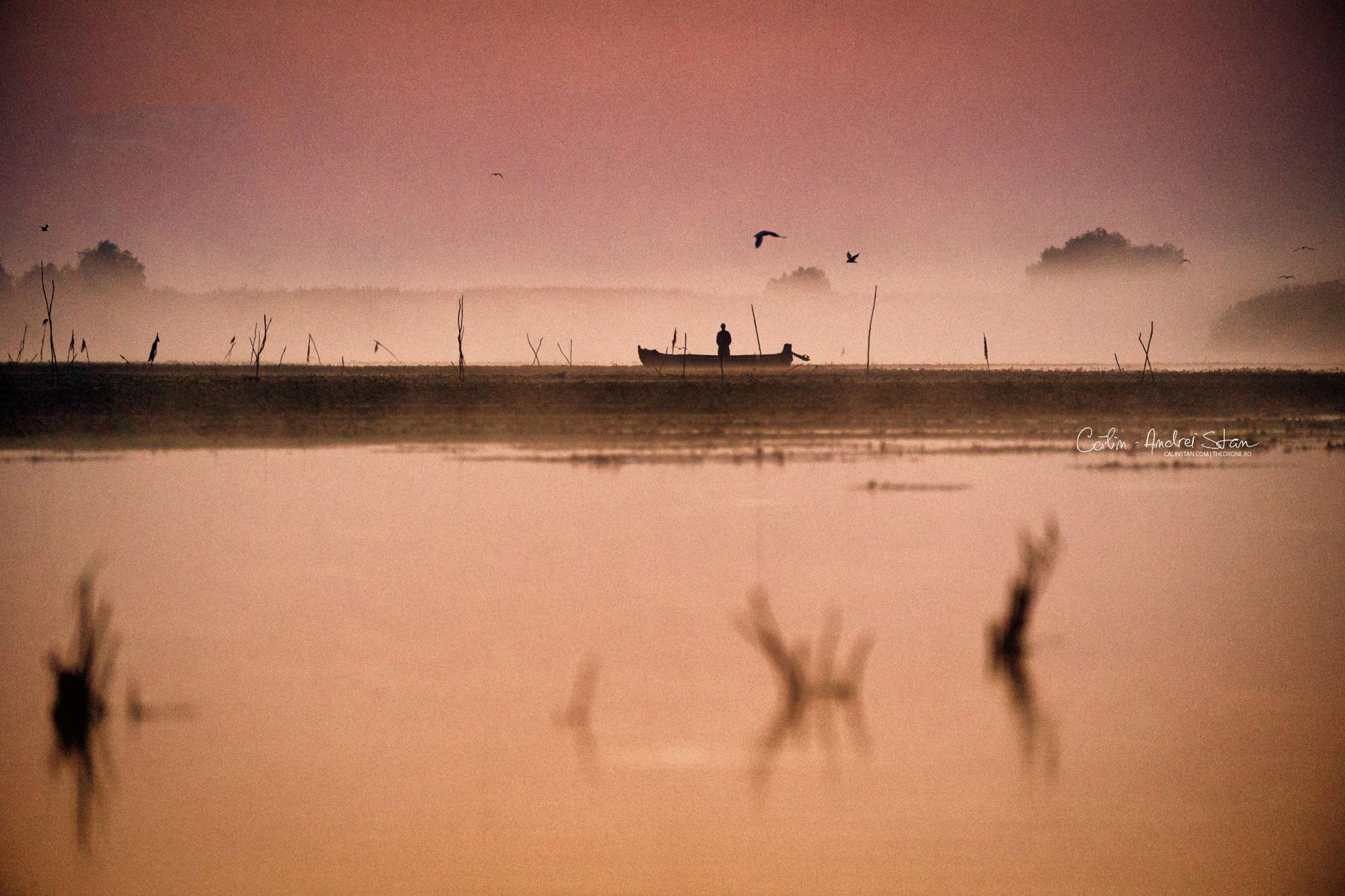 Fotografia originală: pescar în Deltă inspectând plasele, la răsărit